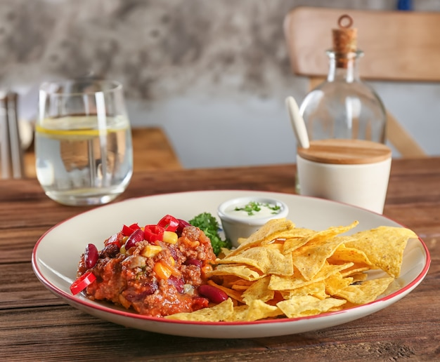 Plate with chili con carne and nacho chips on table