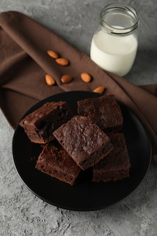 チョコレートケーキのスライス、アーモンド、灰色の背景に牛乳瓶のプレートをクローズアップ