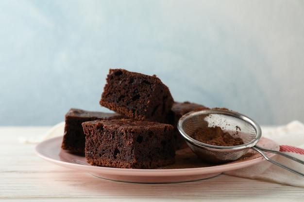 Тарелка с кусочками шоколадного торта и ситечко на деревянный стол с полотенцем, копией пространства