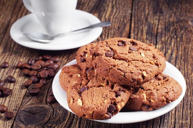 古い木製のテーブルにチョコレートクッキーとコーヒーのカップでプレート