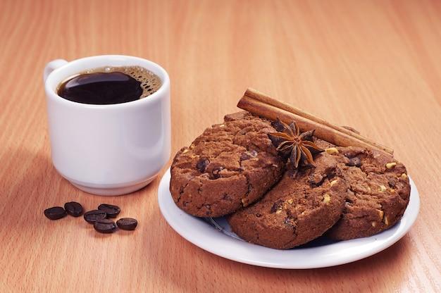 木製のテーブルにチョコレートクッキーとホットコーヒーのカップでプレート