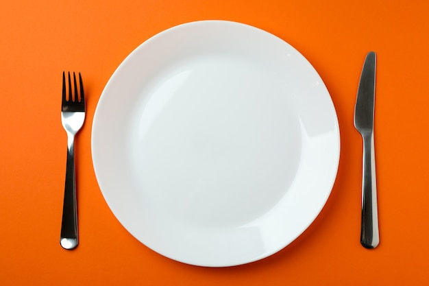 Plate with chocolate piece and cutlery isolated