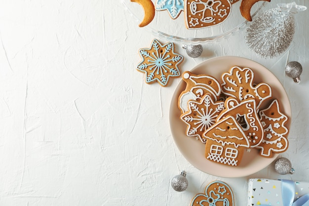 Plate with christmas cookies, christmas trees, toys, gift boxes on white, top view. space for text