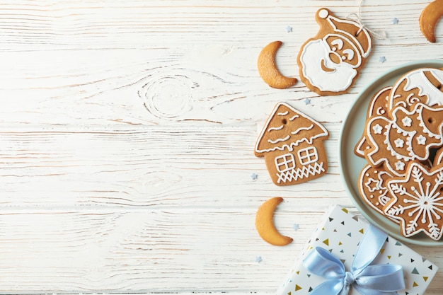 Plate with christmas cookies, gift box on white wooden, space for text. top view