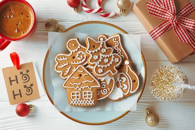 Тарелка с рождественским печеньем, игрушками, подарочными коробками и кофе на белом деревянном, вид сверху
