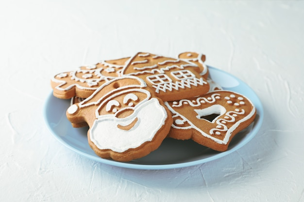 Plate with christmas cookies on white, space for text. closeup