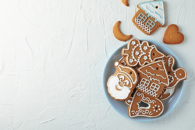 Plate with christmas cookies on white, top view. space for text