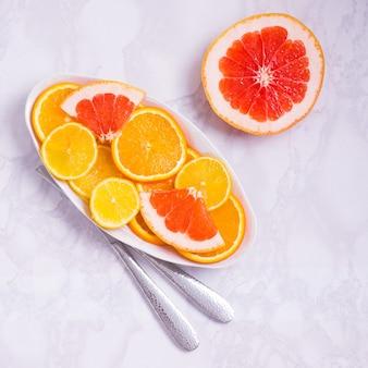 白い背景の上の柑橘類の新鮮な果物でプレート。抗酸化物質、ビタミン、食物繊維、アントカイニンが豊富です。