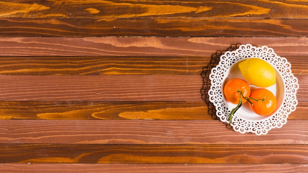 Plate with citrus on wooden table