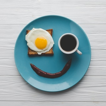 Plate with coffee and fried egg