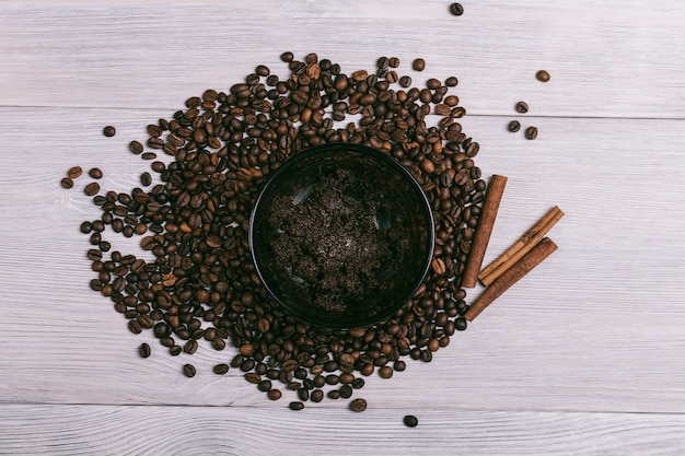 Plate with coffee scrub is on the table among coffee beans
