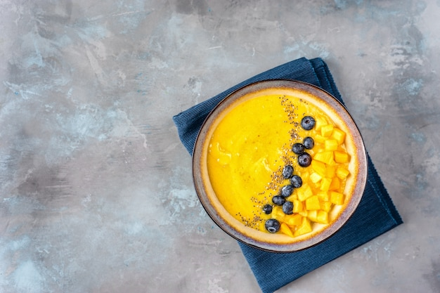 Plate with colorful mango smoothie seeing from above
