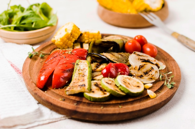 Plate with cooked on barbecue vegetables on table