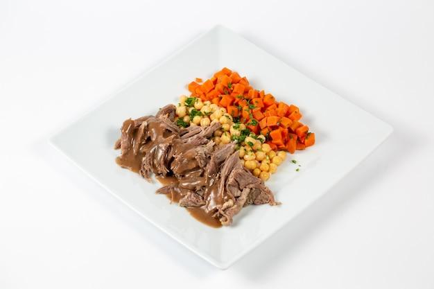 요리 된 쇠고기 완두콩과 당근 소스를 곁들인 접시