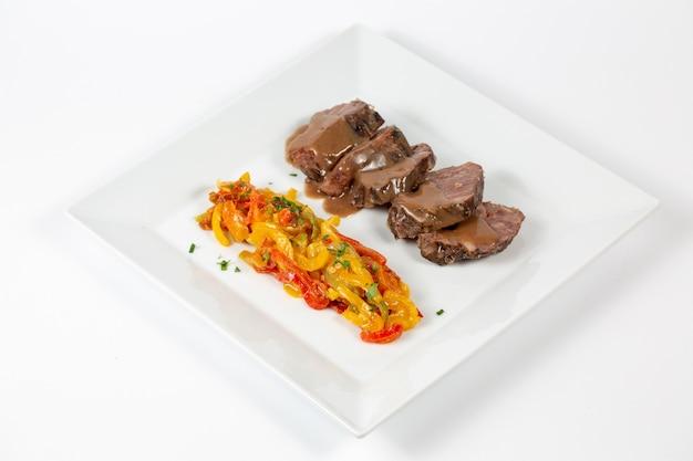 Тарелка с вареной говядиной с нарезанным разноцветным перцем, залитая соусом