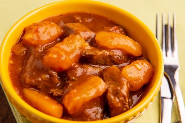 나무 테이블에 요리된 카사바와 고기가 있는 접시.