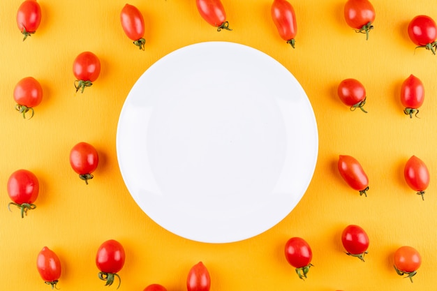Plate with copy space surrounded by red fresh cherry tomatoes on yellow