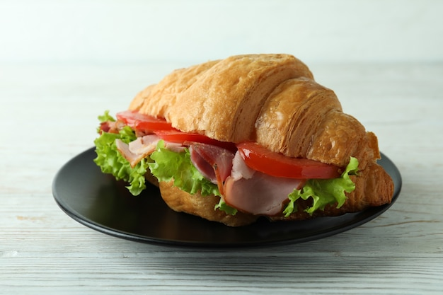 白い木製のテーブルにクロワッサンサンドイッチとプレート