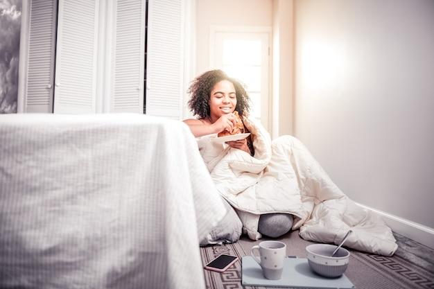 クロワッサンのプレート。彼女の寝室の床に座って、焼きたてのクロワッサンを食べる短い髪の少女の笑顔