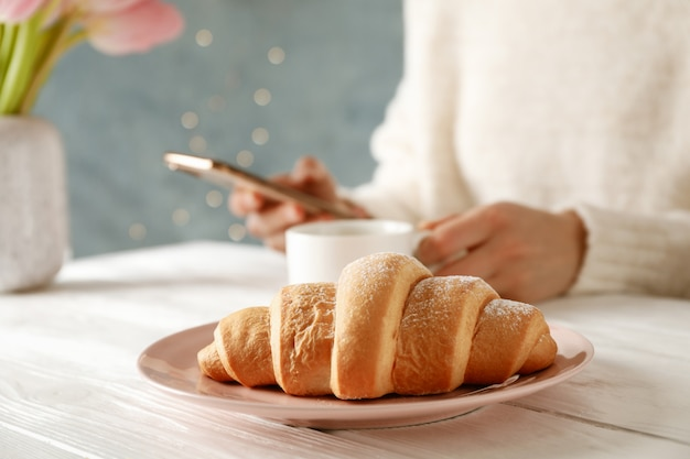 Plate with croissant on wooden table, close up. young woman hold phone