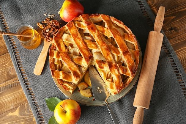 나무 테이블에 맛있는 사과 파이 접시