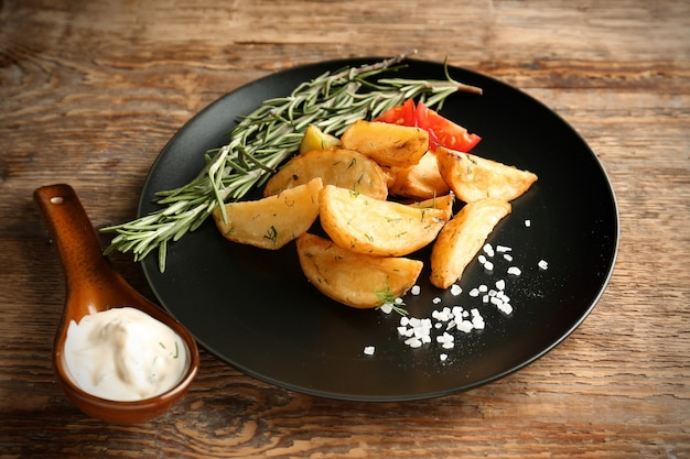 Plate with delicious baked potato wedges and sauce on table