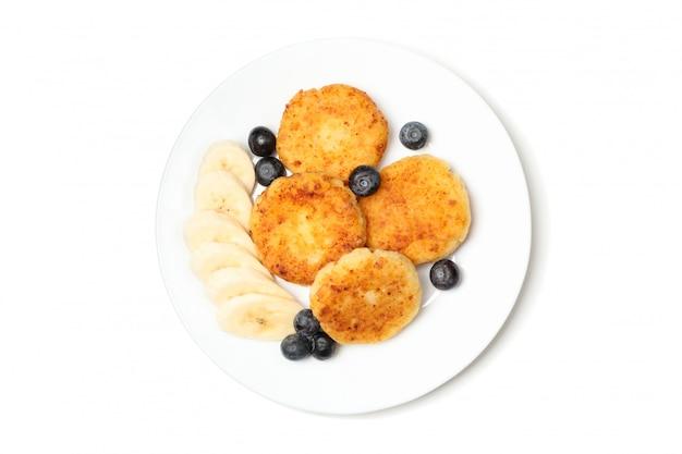 Тарелка с вкусными сырными блинами, изолированные на белой поверхности