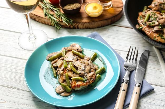 Тарелка с вкусной куриной марсалой и грибами на столе