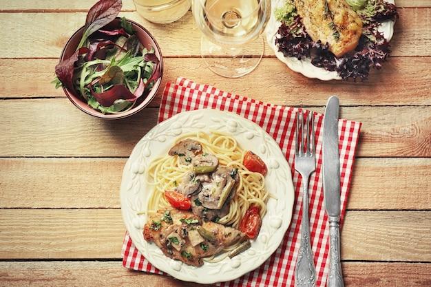 テーブルの上に美味しいチキンマルサラとスパゲッティを添えたプレート