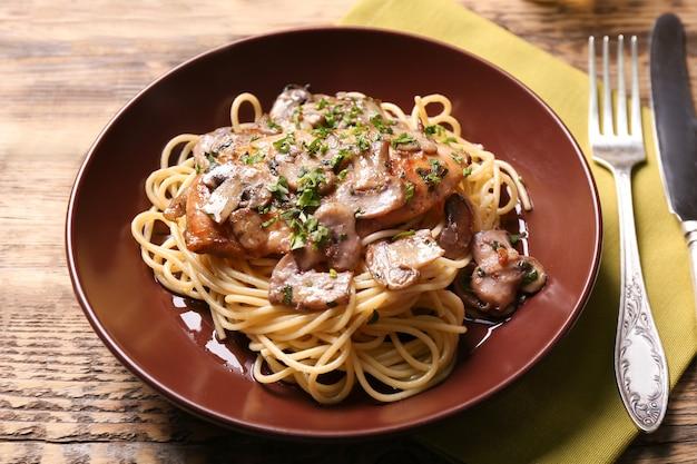 Тарелка с вкусной куриной марсалой и спагетти на столе