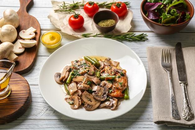 Тарелка с вкусной куриной марсалой и овощами на столе
