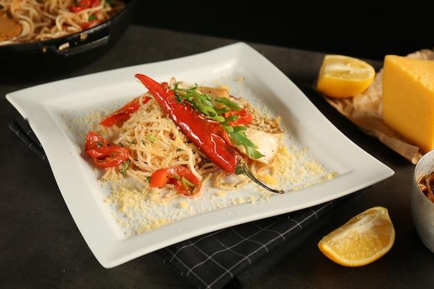 Тарелка с вкусными куриными спагетти на столе