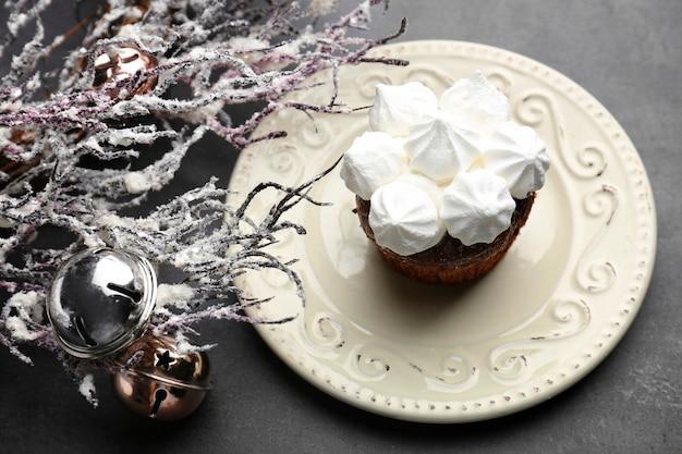 테이블에 맛있는 컵케이크와 크리스마스 장식이 있는 접시