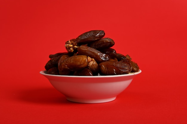 A plate with delicious fresh dates to break the fast in ramadan, isolated on red background, copy space.