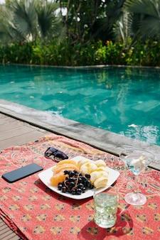 수영장 옆 담요에 맛있는 과일, 칵테일 잔 및 스마트 폰이 담긴 접시