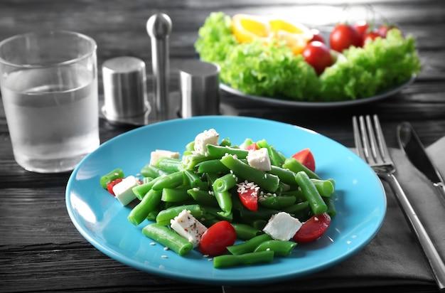 木製のテーブルにおいしいインゲンのサラダを盛り付けます