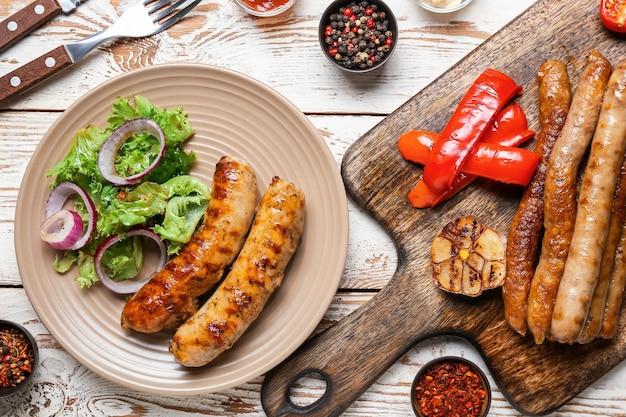 Тарелка с вкусными колбасами на гриле, овощами и специями на деревянном столе