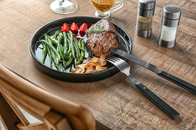 Тарелка с вкусным стейком на гриле и овощами на деревянном столе