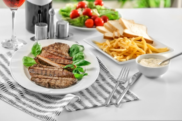 Plate with delicious grilled steak in restaurant