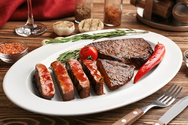 Plate with delicious grilled steaks on wooden table