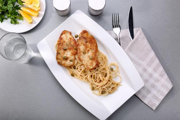 Тарелка с вкусной итальянской куриной пиккатой на столе