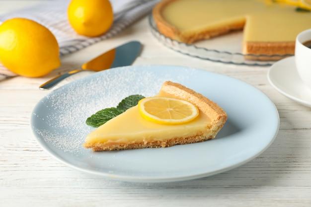 흰색 나무 배경에 맛있는 레몬 타르트 플레이트를 닫습니다