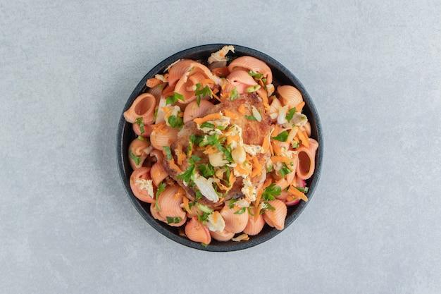 Un piatto con deliziosi maccheroni e carne fritta.