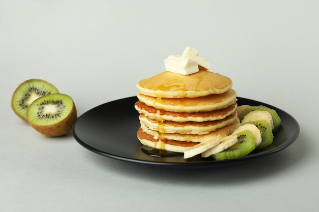 Plate with delicious pancakes and kiwi on gray background