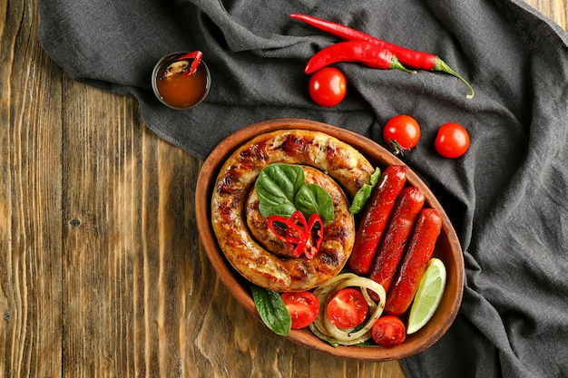 木製のテーブルの上においしいローストソーセージと野菜のプレート