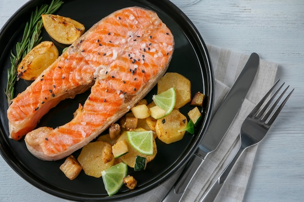 Plate with delicious salmon steak on table