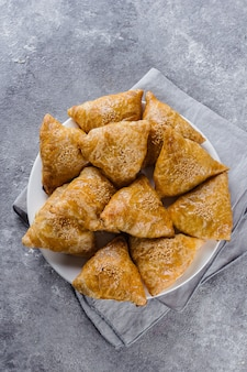 Plate with delicious samosas samsa with meat on gray background, top view. uzbek food