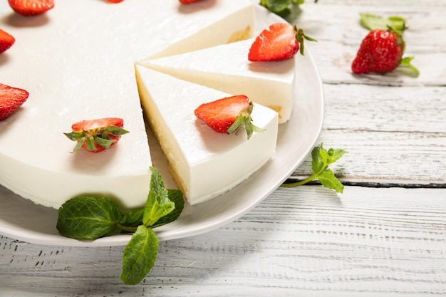 Plate with delicious strawberry cheesecake on a wooden background. close-up.