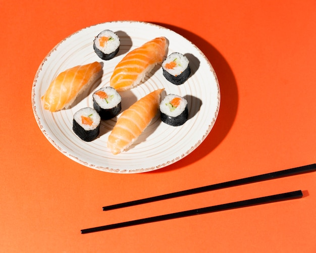 Plate with delicious variety of sushi and chopsticks