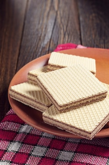 Plate with delicious wafers on a dark wooden table